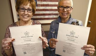Linda Smith and Linda Dodson hold official entry passes to the Macy's Thanksgiving Day Parade as float escorts for the Mount Rushmore's American Pride float during an interview in Hickory, N.C. on Nov. 16, 2018. (Robert C. Reed/The Daily Record via AP)