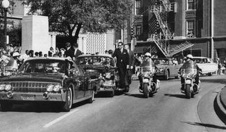 """FILE - In this Nov. 22, 1963, file photo, seen through the foreground convertible's windshield, President John F. Kennedy's hand reaches toward his head within seconds of being fatally shot as first lady Jacqueline Kennedy holds his forearm as the motorcade proceeds along Elm Street past the Texas School Book Depository in Dallas. It has been 55 years since the trauma emergency room at Dallas' Parkland Memorial Hospital became the center of the known universe. Retired Tulsa surgeon Dr. Jerry Gustafson was among the small staff of doctors and others on duty at Parkland on that day. (AP Photo/James W. """"Ike"""" Altgens, File)"""