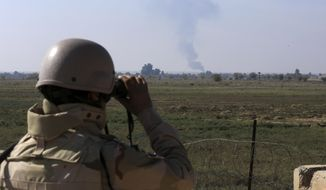 In this Tuesday, Nov. 13, 2018, file photo, an Iraqi soldier watches smoke rising after an airstrike by US-led International coalition warplanes against ISIS, on the border between Syria and Iraq in Qaim, Anbar province, Iraq. (AP Photo/Hadi Mizban)  ** FILE **