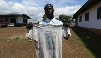 In this photo taken Saturday, Sept. 22, 2018, Moses Z . Kaine, 21 year old , displays a T-Shirt, his father a West Africa peacekeeper, wore to visit his mother, when she was pregnant with him, at a center set up to register and support children left behind by peacekeepers in Liberia, Monrovia. The only memento Moses Z. Kaine has from his father is the T-shirt, left more than two decades ago when the peacekeeper's tour of duty finished and he returned home to leave his pregnant girlfriend behind. (AP Photo/Jonathan Paye -Layleh)