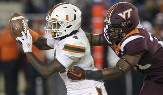 Miami's Jeff Thomas (4) handles a kickoff return while pursued by Virginian Tech defender Chamarri Conner (22) during the second half of an NCAA college football game in Blacksburg, Va., Saturday, Nov. 17 2018. (Matt Gentry/The Roanoke Times via AP)