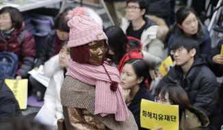 "A statue of a girl representing thousands of Korean women enslaved for sex by Japan's imperial forces before and during World War II, is seen as participants hold signs reading ""Reconciliation and Healing Foundation"" during a weekly rally against Japanese government near the Japanese Embassy in Seoul, South Korea, Wednesday, Nov. 21, 2018. South Korea said Wednesday it will dissolve a foundation funded by Japan to compensate South Korean women who were forced to work in Japan's World War II military brothels. (AP Photo/Lee Jin-man)"