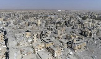 FILE - In this Thursday, Oct. 19, 2017, file photo, an image made from drone video shows damaged buildings in Raqqa, Syria. The rights group Amnesty International is enlisting the help of thousands of online activists to expand its investigation into the U.S-led campaign against Islamic State militants that ended the group's presence in the Syrian city of Raqqa but left it in utter devastation. (AP Photo/Gabriel Chaim, File)