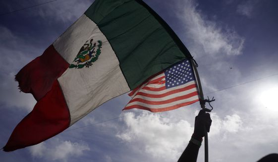 A Honduran migrant holds up Mexican and U.S. flags as he joins a small group of migrants trying to cross the border together at the Chaparral border crossing in Tijuana, Mexico, Thursday, Nov. 22, 2018. (AP Photo/Ramon Espinosa) ** FILE **