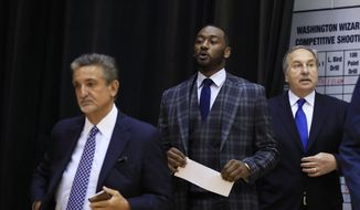 Washington Wizards point guard John Wall, center, with Wizards majority owner Ted Leonsis, left, and president Ernie Grunfeld arrive for a news conference to announce NBA basketball star John Wall's contract extension, Friday, Aug. 4, 2017, in Washington. (AP Photo/Manuel Balce Ceneta) **FILE**