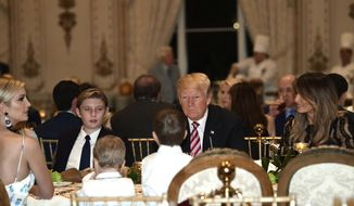 President Donald Trump, center, and first lady Melania Trump, right, sit with their family as they have Thanksgiving Day dinner at their Mar-a-Lago estate in Palm Beach, Fla., Thursday, Nov. 22, 2018. Ivanka Trump, left, and Barron Trump, second from left, attend. (AP Photo/Susan Walsh)
