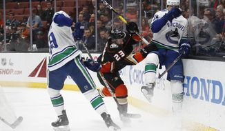 Anaheim Ducks' Brian Gibbons, center, fights for the puck with Vancouver Canucks' Darren Archibald, left, and Adam Gaudette during the first period of an NHL hockey game Wednesday, Nov. 21, 2018, in Anaheim, Calif. (AP Photo/Jae C. Hong)