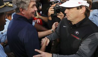 FILE - In this nov. 25, 2017, file photo, Georgia Tech head coach Paul Johnson, left, and Georgia head coach Kirby Smart greet each other after Georgia beat Georgia Tech 38-7 in a NCAA college football game in Atlanta. Neither coach seems to think it'll be possible to slow down the other team in Saturday's state rivalry game. (Curtis Compton/Atlanta Journal-Constitution via AP, File)