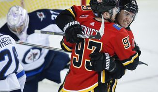 Calgary Flames' Sam Bennett (93) celebrates his goal with teammate Matthew Tkachuk, right, as Winnipeg Jets goalie Connor Hellebuyck picks himself up during the first period of an NHL hockey game Wednesday, Nov. 21, 2018, in Calgary, Alberta. (Jeff McIntosh/The Canadian Press via AP)