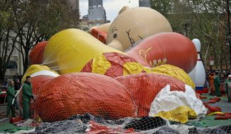 Giant character balloons, including Charlie Brown, are being inflated the night before their appearance in the 92nd Macy's Thanksgiving Day parade, Wednesday Nov. 21, 2018, in New York. (AP Photo/Bebeto Matthews)