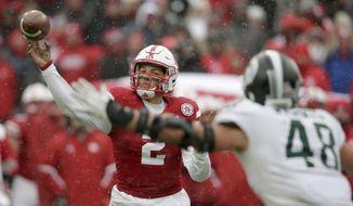 Nebraska quarterback Adrian Martinez (2) throws a pass as Michigan State defensive end Kenny Willekes (48) closes in, during the second half of an NCAA college football game in Lincoln, Neb., Saturday, Nov. 17, 2018. Nebraska won 9-6. (AP Photo/Nati Harnik)