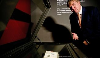 Dutch King Willem-Alexander looks at Anne Frank's diary displayed in the new Diary Room at the renovated Anne Frank House Museum in Amsterdam, Netherlands, Thursday, Nov. 22, 2018. The museum is built around the secret annex hidden in an Amsterdam canal-side house where teenage Jewish diarist Anne Frank hid from Nazi occupiers during World War II is expanding to better tell Anne's tragic story to the growing number of visitors. (Patrick van Katwijk, pool photo via AP)