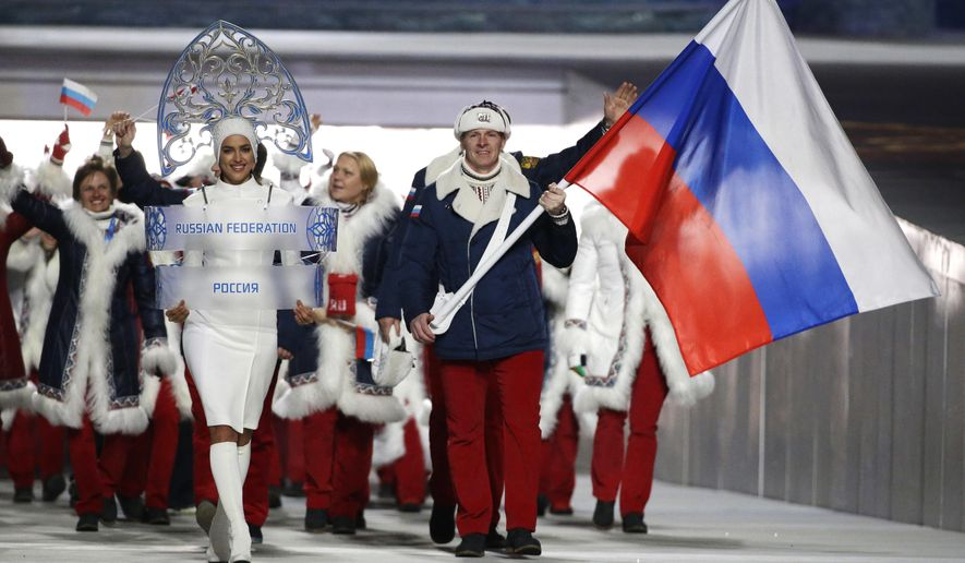FILE - In this Feb. 7, 2014 file photo Alexander Zubkov of Russia carries the national flag as he leads the team during the opening ceremony of the 2014 Winter Olympics in Sochi, Russia. The Moscow City Court ruled on Wednesday Nov. 21, 2018, that Alexander Zubkov, who carried the Russian flag at the opening ceremony of the 2014 Winter Olympics in Sochi, should still be considered an Olympic champion, but the International Olympic Committee refuses to recognize the verdict. (AP Photo/Mark Humphrey, file)