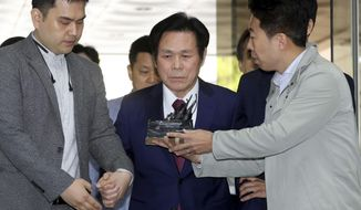 In this May 3, 2018 photo, A South Korean pastor Lee Jae-rock, center, is questioned by reporters upon his arrival for hearing at the Seoul Central District Court in Seoul, South Korea. Lee has been sentenced to 15 years in prison for raping or sexually molesting eight female followers who believed he was God. (Ko Bum-jun/Newsis via AP)