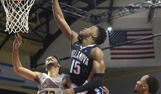 Villanova forward Saddiq Bey (15) goes up for a shot between Canisius guard Isaiah Reese (13) and guard Takal Molson, right, during the second half of an NCAA college basketball game Thursday, Nov. 22, 2018, in Kissimmee, Fla. (AP Photo/Phelan M. Ebenhack)