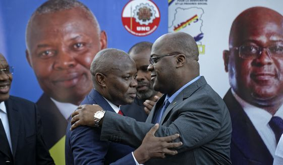 Felix Tshisekedi, right, of Congo's Union for Democracy and Social Progress opposition party, hugs Vital Kamerhe, left, of Congo's Union for the Congolese Nation opposition party, after being endorsed Kamerhe at a press conference in Nairobi, Kenya Friday, Nov. 23, 2018. Congo's two leading opposition parties announced Friday they are joining forces for a run at the presidency after withdrawing from a wider pact to support a single contender to take on President Joseph Kabila's chosen candidate. (AP Photo/Ben Curtis)