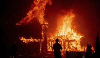 FILE - In this Thursday, Nov. 8, 2018 file photo, a home burns as the Camp Fire rages through Paradise, Calif. Authorities say the fire is 95 percent contained Thursday, Nov. 22. The deadly blaze that started Nov. 8 leveled Paradise, killing multiple people and destroyed thousands of homes. (AP Photo/Noah Berger, File)