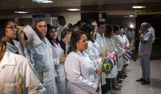 """Cuban doctors assemble to meet Cuba's President Miguel Diaz-Canel after landing in Havana, Cuba, Friday, Nov. 23, 2018. The first group of departing Cuban doctors left Brazil Friday after Cuba recalled more than 8,000 doctors rather than meet conditions imposed by Brazilian President-elect Jair Bolsonaro, who said the """"More Doctors"""" program could continue only if doctors' pay isn't channeled through the Cuban government and if they could bring their families. (AP Photo/Desmond Boylan)"""