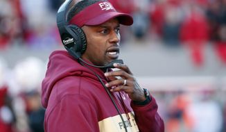 FILE- In this Nov. 3, 2018, file photo Florida State head coach Willie Taggart confers on his headset during the first half of an NCAA college football game against North Carolina State in Raleigh, N.C. The Seminoles have a chance to salvage their season against No. 13 Florida (8-3, No. 11 CFP) in Tallahassee on Saturday, Nov. 24. (AP Photo/Chris Seward, File)