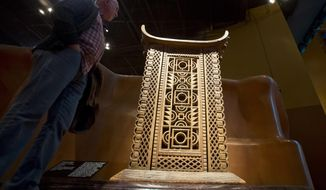 A visitor looks at the wooden and metal throne of the King Ghezo of the Dahomey kingdom, dated 19th century, today's Benin at Quai Branly museum in Paris, France, Friday, Nov. 23, 2018. From Senegal to Ethiopia, artists, governments and museums are eagerly awaiting a report commissioned by French President Emmanuel Macron on how former colonizers can return African art to Africa. (AP Photo/Michel Euler)