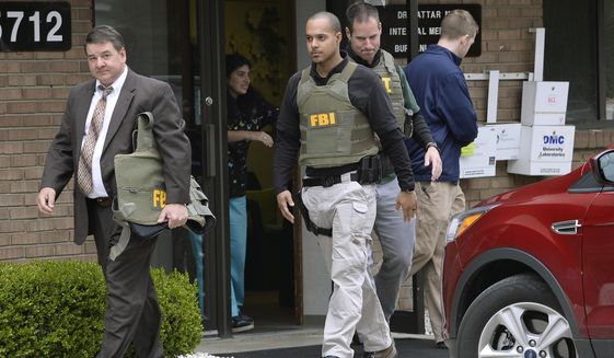 FILE - In this April 21, 2017 file photo, FBI agents leave the office of Dr. Fakhruddin Attar at the Burhani Clinic in Livonia, Mich., after completing a search for documents. A federal judge dismissed some charges Tuesday, Nov. 20, 2018, against eight people, including two doctors, in the genital mutilation of nine girls at the suburban Detroit clinic, finding it's up to states rather than Congress to regulate the practice. (Clarence Tabb Jr. /Detroit News via AP, File)