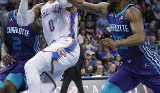 Oklahoma City Thunder guard Russell Westbrook (0) is fouled on the way to the basket by Charlotte Hornets guard Kemba Walker (15) during the second half of an NBA basketball game in Oklahoma City, Friday, Nov. 23, 2018. Oklahoma City won 109-104. (AP Photo/Alonzo Adams)