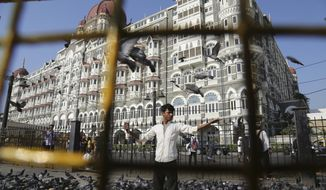 In this Nov 17, 2018, photo, a man feeds pigeons outside the iconic Taj Mahal Palace hotel, the epicenter of the 2008 terror attacks that killed 166 people in Mumbai, India. Thirty-one people died inside the hotel, including staff trying to guide the guests to safety. Visceral images of smoke leaping out of the city landmark have come to define the 60-hour siege. (AP Photo/Rafiq Maqbool)