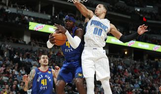 Denver Nuggets forward Paul Millsap, center left, pulls in a rebound as Orlando Magic forward Aaron Gordon (00) defends in the first half of an NBA basketball game Friday, Nov. 23, 2018, in Denver. (AP Photo/David Zalubowski)