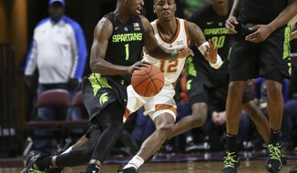 Michigan State's Joshua Langford (1) moves the ball around Texas' Kerwin Roach II (12) during the first half of an NCAA college basketball game Friday, Nov. 23, 2018, in Las Vegas. (AP Photo/Chase Stevens)