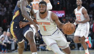 New York Knicks guard Emmanuel Mudiay (1) on the fast break with New Orleans Pelicans guard Jrue Holiday (11) in the third quarter of an NBA basketball game, Friday, Nov. 23, 2018, in New York. (AP Photo/Howard Simmons)