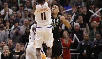 Phoenix Suns' Jamal Crawford (11) hits the game-winning shot over Milwaukee Bucks' Malcolm Brogdon during the second half of an NBA basketball game Friday, Nov. 23, 2018, in Milwaukee. The Suns won 116-114. (AP Photo/Jeffrey Phelps)