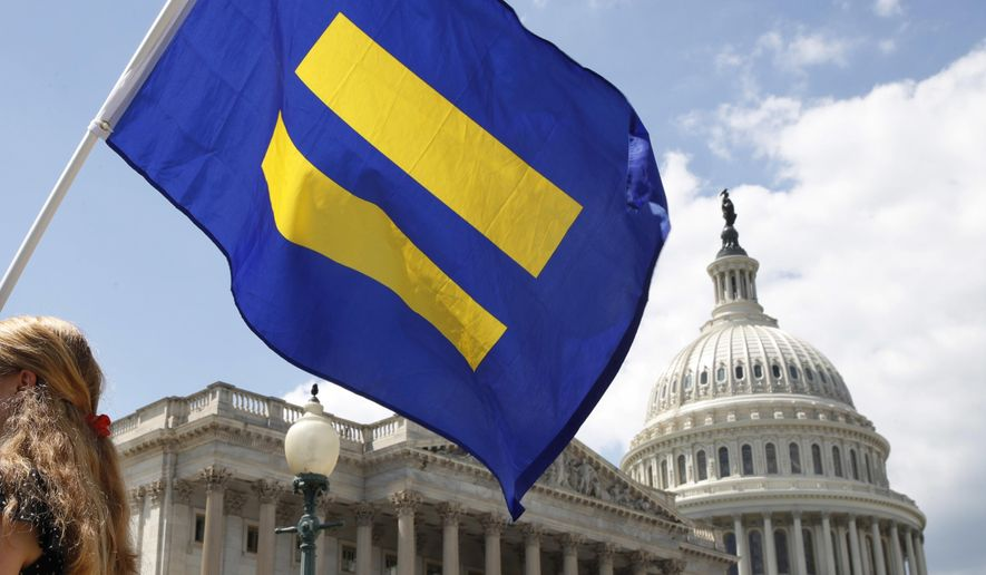 """In this July 26, 2017, file photo, a supporter of LGBT rights holds up an """"equality flag"""" on Capitol Hill in Washington, during an event held by Rep. Joe Kennedy, D-Mass., in support of transgender members of the military. (AP Photo/Jacquelyn Martin, File)"""