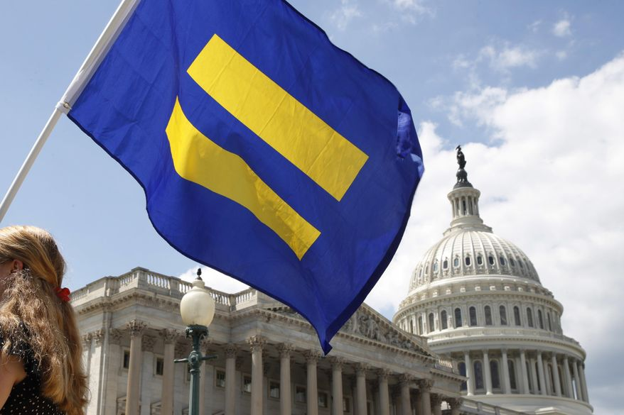 "In this July 26, 2017, file photo, a supporter of LGBT rights holds up an ""equality flag"" on Capitol Hill in Washington, during an event held by Rep. Joe Kennedy, D-Mass., in support of transgender members of the military. (AP Photo/Jacquelyn Martin, File)"