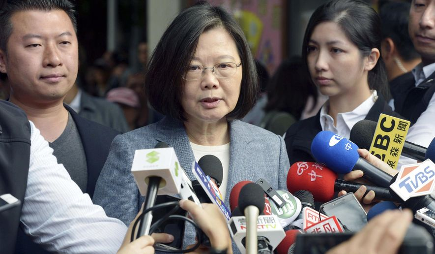 Taiwanese President Tsai Ing-wen, center, speaks to journalists after a vote in local elections in New Taipei City, Taiwan Saturday, Nov. 24, 2018. Taiwanese have begun voting in midterm local elections seen as a referendum on the administration of President Tsai, amid growing pressure from the island's powerful rival China. (Kyodo News via AP)
