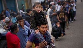 A migrant child playfully sticks out his tongue as others stand in line to receive food outside the Benito Juarez Sports Center serving as a temporary shelter for Central American migrants who traveled north in a caravan, in Tijuana, Mexico, Saturday, Nov. 24, 2018. The mayor of Tijuana has declared a humanitarian crisis in his border city and says that he has asked the United Nations for aid to deal with the approximately 5,000 Central American migrants who have arrived in the city. (AP Photo/Ramon Espinosa)