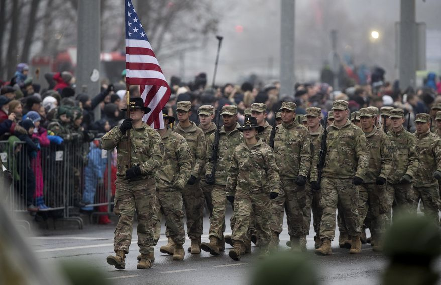Members of the U.S. Army march during a military parade ceremony marking the 100th anniversary of the Lithuanian military on Armed Forces Day in Vilnius, Lithuania, Saturday, Nov. 24, 2018. For Lithuanians, the holiday honours the restoration of the country's armed forces in 1918 after the end of WWI. (AP Photo/Mindaugas Kulbis)