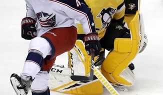 Columbus Blue Jackets' Scott Harrington (4) celebrates his goal on Pittsburgh Penguins goaltender Casey DeSmith (1) during the first period of an NHL hockey game in Pittsburgh, Saturday, Nov. 24, 2018. (AP Photo/Gene J. Puskar)