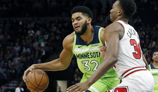 Minnesota Timberwolves' Karl-Anthony Towns, left, works around Chicago Bulls' Wendell Carter Jr. in the first half of an NBA basketball game Saturday, Nov. 24, 2018, in Minneapolis. (AP Photo/Jim Mone)