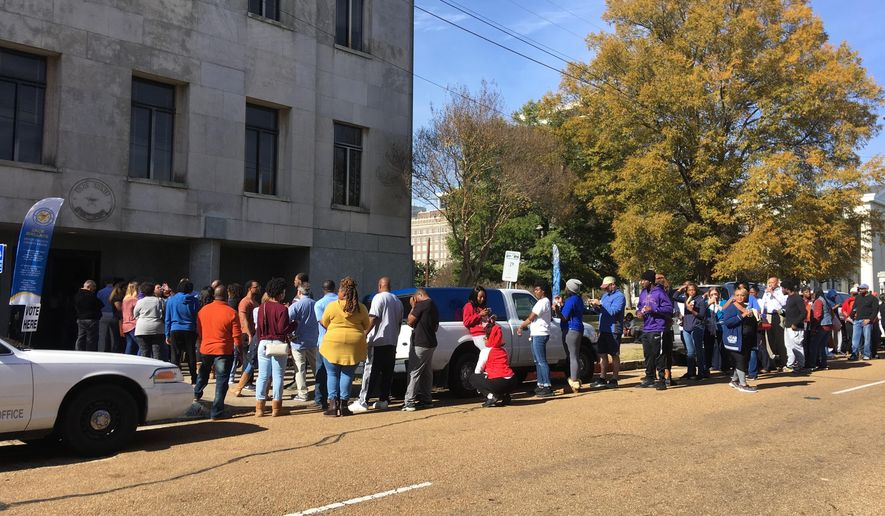 Several dozen people stand in line outside the Hinds County Courthouse in Jackson, Miss., on Saturday, Nov. 24, 2018, waiting to cast absentee ballots in a U.S. Senate election runoff between Republican Sen. Cindy Hyde-Smith and Democrat Mike Espy. Saturday was the deadline for people to cast absentee ballots at circuit clerks' offices, and it is unusual to see lines on the absentee deadline day. The runoff election is Tuesday, Nov. 27, 2018, and the winner will serve the final two years of a six-year term started by longtime Sen. Thad Cochran. Mississippi's Republican governor appointed Hyde-Smith to serve temporarily when Cochran retired because of health concerns. (AP Photo/Emily Wagster Pettus)