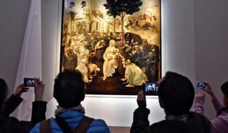 """FILE - In this Monday, March 27, 2017 file photo, visitors take pictures of Leonardo da Vinci's """"Adoration of the Three Wise Men"""", returned to the public of the Uffizi museum after 6 years of study and restoration, in Florence, Italy. Leonardo da Vinci is often hailed as the most universal genius. Not for Italy's nationalist government, which is livid that the Louvre is counting on Italian museums to lend many of the native Italian native's masterpieces for a blockbuster exhibit in Paris. (Maurizio Degl'Innocenti/ANSA via AP, File)"""