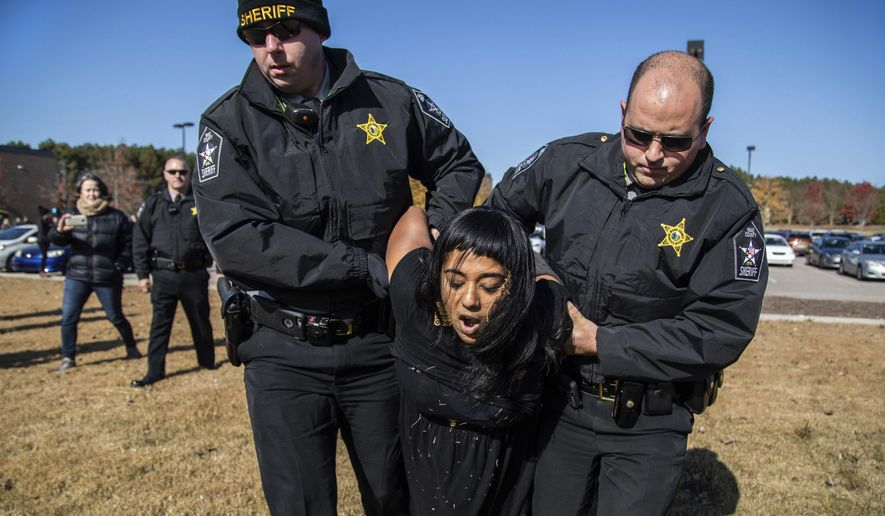 A demonstrator is arrested after Samuel Oliver-Bruno, 47, an undocumented Mexican national, was arrested after arriving at an appointment with immigration officials, in Morrisville, N.C., Friday, Nov. 23, 2018. He had been living in CityWell United Methodist Church in Durham since late 2017 to avoid the reach of immigration officers, who generally avoid making arrests at churches. (Travis Long/The News & Observer via AP) **FILE**