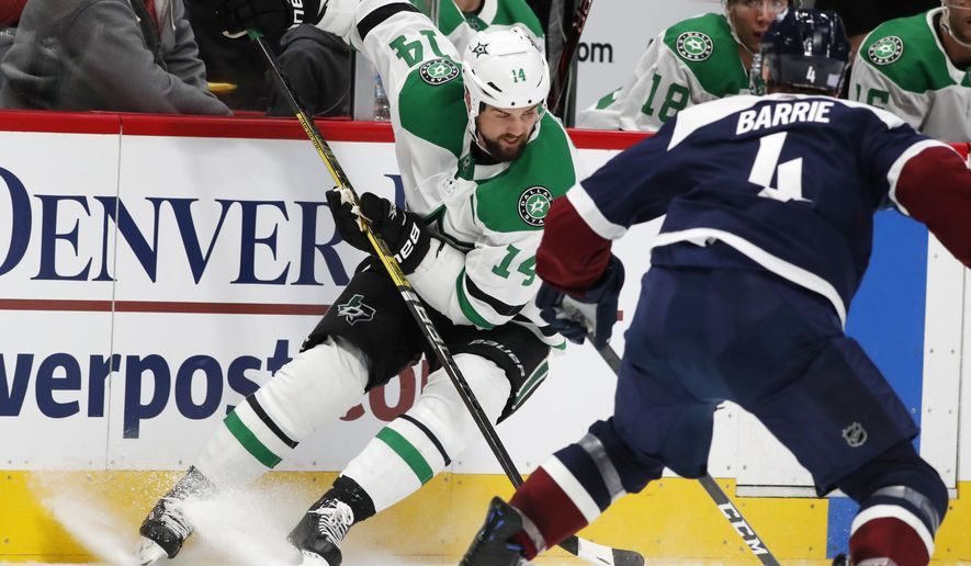 Dallas Stars left wing Jamie Benn, back, looks to pass the puck as Colorado Avalanche defenseman Tyson Barrie covers in the second period of an NHL hockey game Saturday, Nov. 24, 2018, in Denver. (AP Photo/David Zalubowski)