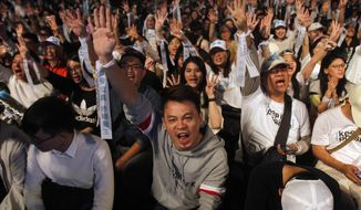 Supporters of Taipei city mayor and city mayoral candidate Ko Wen-je cheer in Taipei, Taiwan, Saturday, Nov. 24, 2018. Taiwan's ruling party suffered a major defeat Saturday in local elections seen as a referendum on the administration of the island's independence-leaning president amid growing economic and political pressure from China. (AP Photo/Chiang Ying-ying)