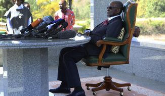 FILE - In this Sunday, July 29, 2018 file photo, former Zimbabwean President Robert Mugabe holds a press briefing at his residence in Harare. Zimbabwe's former president Robert Mugabe is no longer able to walk as his health declines, his successor says. President Emmerson Mnangagwa told ruling party supporters at a rally Saturday, Nov. 24 that the 94-year-old Mugabe has been in a hospital in Singapore for the past two months. (AP Photo/Tsvangirayi Mukwazhi, file)