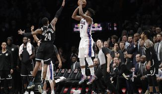Philadelphia 76ers' Jimmy Butler (23) hits a game-winning three-point shot over Brooklyn Nets' Rondae Hollis-Jefferson (24) in the fourth quarter of an NBA basketball game, Sunday, Nov. 25, 2018, in New York. The 76ers won 127-125. (AP Photo/Mark Lennihan)