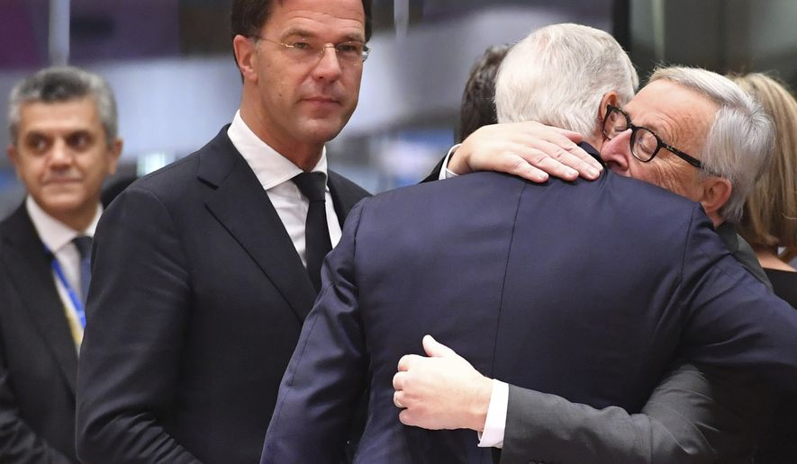 European Commission President Jean-Claude Juncker, right, embraces European Union chief Brexit negotiator Michel Barnier during a round table meeting at an EU summit in Brussels, Sunday, Nov. 25, 2018. European Union leaders are gathering to seal an agreement on Britain's departure from the bloc next year, the first time a member country will have left the 28-nation bloc. (AP Photo/Geert Vanden Wijngaert)