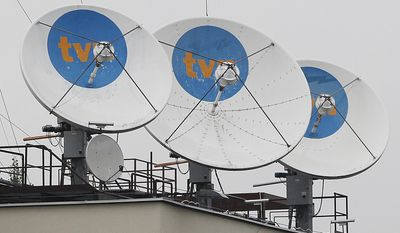 FILE- In this file photo taken Sept. 12, 2017, satellite dishes sit on top of the headquarters of the private TVN broadcaster in Warsaw, Poland is owned by the U.S. Scripps Networks Interactive. Poland's state regulator imposed a heavy fine on TVN alleging it was unfair for its coverage of 2016 anti-government protests.  (AP Photo/Czarek Sokolowski, file)