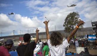 Migrants wave at U.S. border control helicopters flying near the Benito Juarez Sports Center serving as a temporary shelter for Central American migrants, in Tijuana, Mexico, Saturday, Nov. 24, 2018. The mayor of Tijuana has declared a humanitarian crisis in his border city and says that he has asked the United Nations for aid to deal with the approximately 5,000 Central American migrants who have arrived in the city.