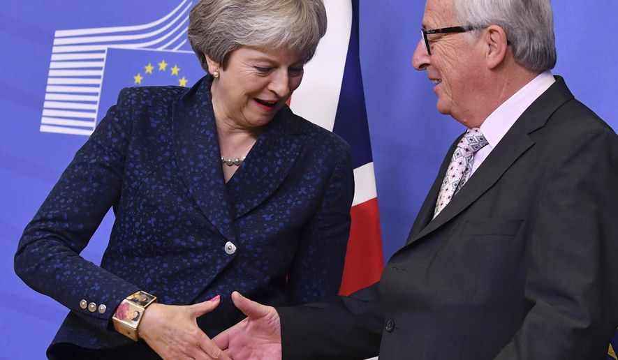 European Commission President Jean-Claude Juncker, right, shakes hands with British Prime Minister Theresa May prior to a meeting at EU headquarters in Brussels, Saturday, Nov. 24, 2018. British Prime Minister Theresa May is kicking off a big Brexit weekend by traveling to EU headquarters in Brussels for talks on Saturday with key leaders. (AP Photo/Geert Vanden Wijngaert)