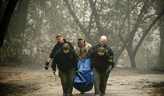 FILE - In this Nov. 10, 2018, file photo, sheriff's deputies recover the remains of a victim of the Camp Fire in Paradise, Calif. The massive wildfire that killed dozens of people and destroyed thousands of homes has been fully contained after burning for more than two weeks, authorities said Sunday, Nov. 25. (AP Photo/Noah Berger, File)